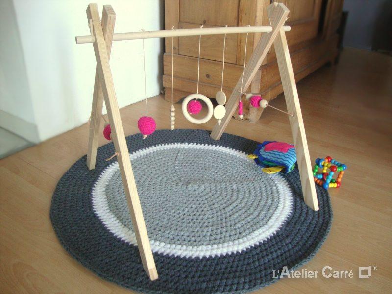 portique d'éveil bois et crochet fuschia
